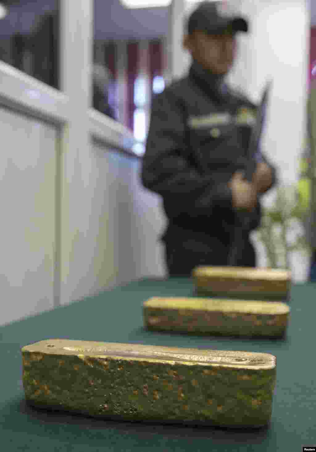 An armed guard stands by as gold alloy bars are put on display.