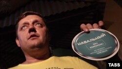 Депутат Олег Пахолков демонстрирует стикер в поддержку Алексея Навального, изъятый из квартиры сторонников кандидата в мэры Москвы