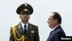 Armenia -- French President Francois Hollande walks past an honor guard as he attends a commemoration ceremony marking the centenary of the Armenians genocide in Yerevan, April 24, 2015