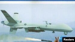 АҚШ-қа қарсы наразылық жиынына қатысушы адам америкалық әскери ұшақ бейнеленген сурет жанында тұр. Карачи, Пәкістан, 4 маусым 2011 ж. (Көрнекі сурет)