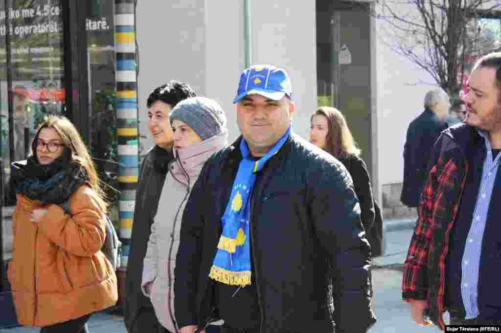 Një burrë ka veshur një kapelë dhe shall me simbolet shtetërore të Kosovës