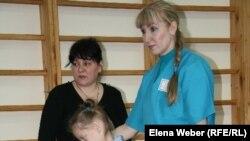 Инструктор по лечебной физкультуре проводит занятия с ребенком-инвалидом. Темиртау, 4 декабря 2010 года.