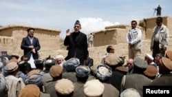Afghanistan -- President Hamid Karzai (2nd L) speaks to displaced villagers during his visit at the site of a deadly landslide in the Argo district of Badakhshan province, May 7, 2014