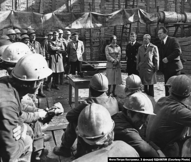 Яўгенія Янішчыц, Яўген Каршукоў (стаіць першы справа) і Міхась Скрыпка (стаіць другі справа) выступаюць перад будаўнікамі менскага мэтро. 1980-я гг. Фота Пятра Кастрамы. З фондаў БДАМЛіМ