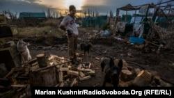 Український військовослужбовець із позивним «Піксель» рубає дрова посеред села Піски