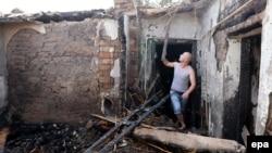 Сотрудник министерства по чрезвычайным ситуациям Кыргызстана осматривает дом, разрушенный в ходе спецоперации по ликвидации террористической группировки. Бишкек, 17 июля 2015 года.