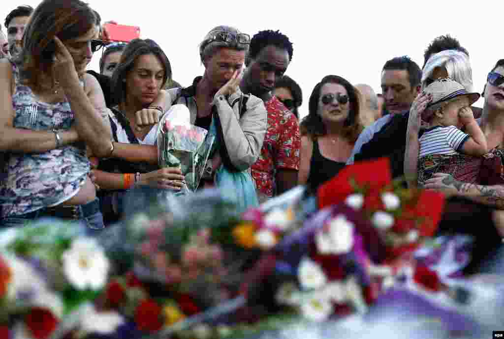 A woman cries as people gather in front of a memorial on the Promenade des Anglais in Nice, France, where on July 14 a truck crashed into a crowd during Bastille Day celebrations, killing at least 84 people in an attack claimed by Islamic State. (epa/Ian Langsdon)
