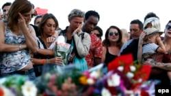 Люди плачут на месте теракта в Ницце. 15 июля 2016 года.