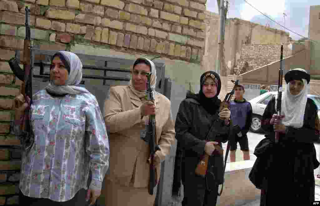 Armed members of the Women's Association linked to the ruling Ba'ath party stand at the entrance to their party's building in Baghdad on March 23.