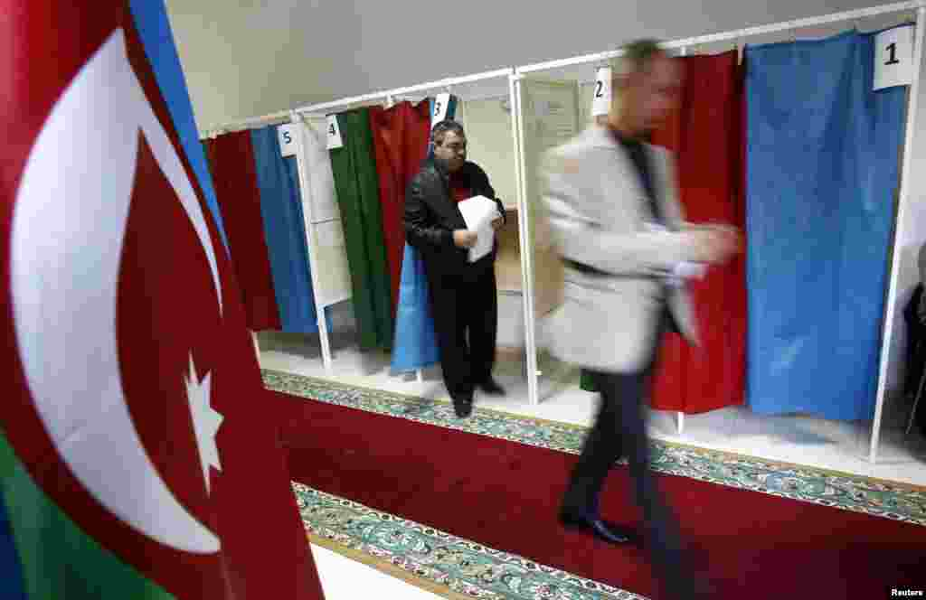 People leave the voting booths during the presidential election at a polling station in Baku.