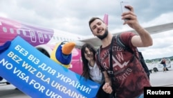 Passengers take selfies as they arrive from Kyiv after the European Union granted visa-free travel for Ukrainian citizens at the airport in Gdansk, Poland, in June 2017.