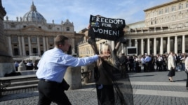 A Femen activist is stopped by security in front of St Peter's Basilica in Rome in November.