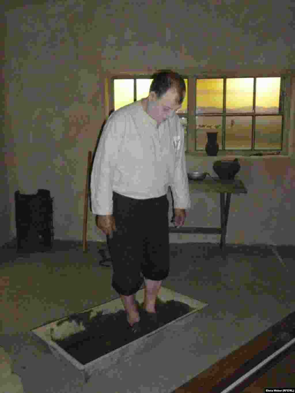A museum employee demonstrates how hungry and exhausted prisoners used to churn clay with their feet to make mud bricks.