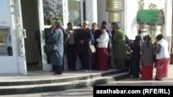 Türkmenistanda daşary ýurtdaky dogan-garyndaşlary üçin pul ibermek üçin bankyň öňünde nobata duran adamlar. Illýustrasiýa suraty