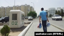 Turkmenistan -- Boy carrying the pack of water. Police box. Ashgabat. June 9, 2014