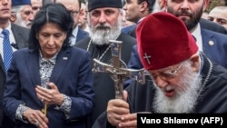 Georgian President Salome Zurabishvili (left) and Georgian Orthodox Patriarch Ilia II take part in a prayer during a commemoration ceremony in Tbilisi.