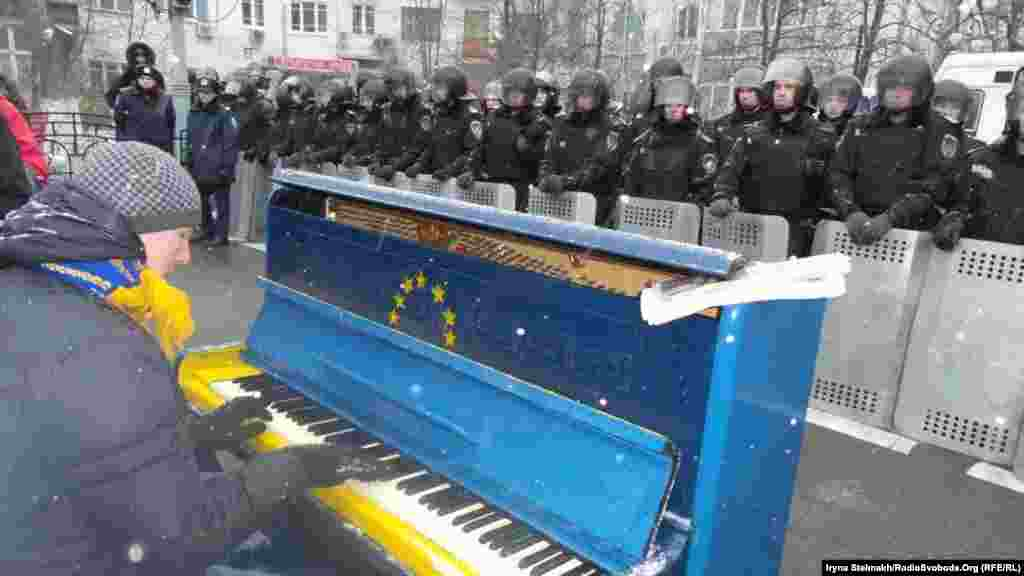 A pro-EU protester plays the piano near the presidential administration in Kyiv. (RFE/RL / Iryna Slelmakh)