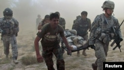 U.S. and Afghan troops carry a wounded U.S. soldier through a dust cloud to a helicopter after he was injured by a roadside bomb in Kandahar Province on October 13.