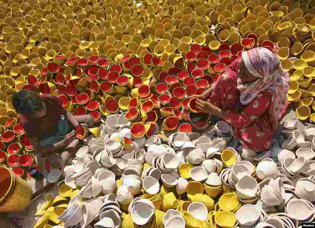 Potters color earthen lamps at a workshop ahead of the Hindu festival of Diwali in the northern Indian city of Amritsar on October 15. (Reuters/Munish Sharma)