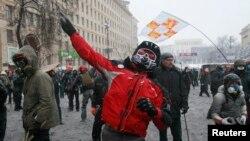 Участники антиправительственных протестов бросают камни в сторону милиции. 22 января 2014 года.
