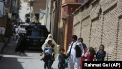 Families leave their homes after a rocket strike in the western part of Kabul on July 24.