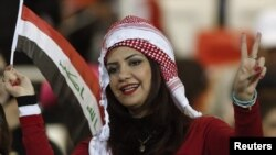 Bahrain - A fan of Iraq watches her team play during their Gulf Cup tournament final soccer match against UAE in Isa Town, 18Jan2013