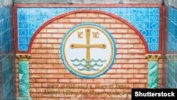 Пам'ятний знак у Києві. Місце хрещення України-Русі. Панно з кераміки, що зображує хрест на водах Дніпра (символ хрещення) і напис: «Тут в 988 році на злитті Дніпра і Почайни хрестилася Русь»