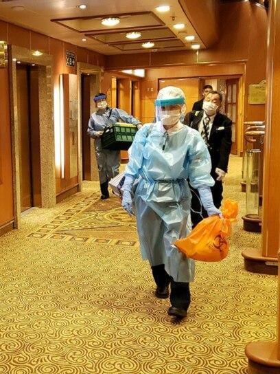Muškarci u zaštitnoj odjeći na hodnicima kruzera Diamond Princess. Skoro 3.700 ljudi zatvoreno je na plovilu otkada je 4. veljače nekim putnicima dijagnosticiran visoko zarazni koronavirus.