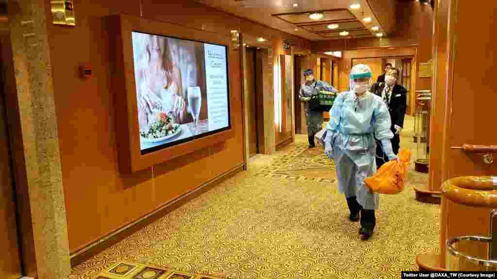 Muškarci u zaštitnoj odjeći na hodnicima kruzera Diamond Princess (Dijamantna princeza). Skoro 3.700 ljudi zatvoreno je na plovilu otkada je 4. veljače nekim putnicima dijagnosticiran visoko zarazni koronavirus.