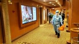Мужчины в защитной одежде внутри круизного лайнера Diamond Princess. Почти 3 700 людей стали заложниками поневоле. Они оказались запертыми на судне после 4 февраля, вслед за тем, как у некоторых пассажиров выявили высокопатогенный коронавирус.