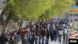 This recent undated photo from Iran shows few people are wearing masks.