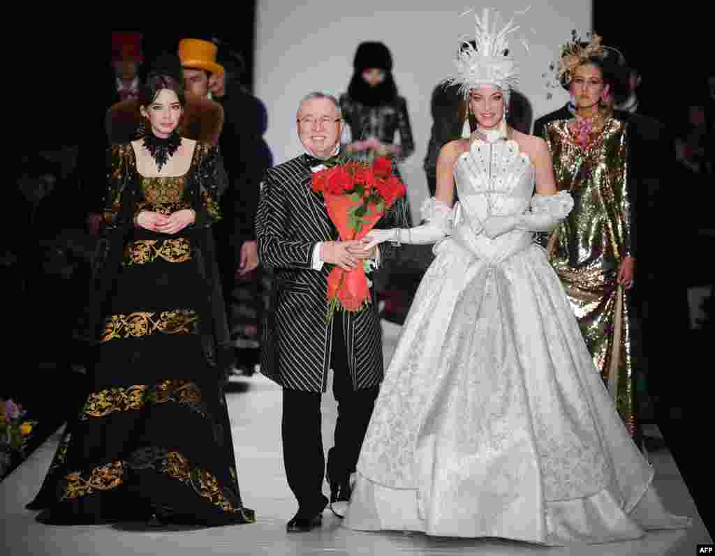 Russian fashion designer Slava Zaitsev (center) walks on stage surrounded by models.