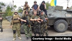 Isa Munaev (3rd from left) poses for a photo in Ukraine with members of his battalion.