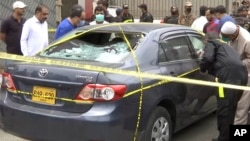 Полиция вакиллари ҳужумчилар машинасини атрофида йиғилмоқда, Карачи, 2020 йил 29 июни.