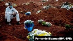 Работник кладбища в Сан-Паулу, Бразилия. За 12 часов было погребено 62 человека. 18 мая 2020 года.