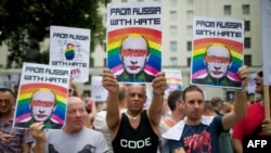 Protesters holding anti-Vladimir Putin posters march past the British prime minister's residence on Downing Street in central London on August 10.