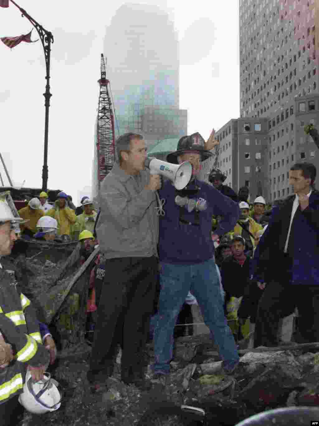 The day after - U.S. President George W. Bush (left) speaks through a megaphone beside retired firefighter Bob Beckwith, 69, to firemen and other workers on September 14, 2001, at the site of the destroyed World Trade Center in New York.