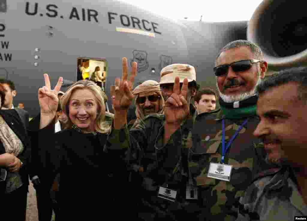 Secretary of State Hillary Clinton (left) gestures with Libyan soldiers upon her departure from Tripoli, Libya, on October 18, 2011.
