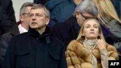 دیمیتری ریبولُولُف [در کنار زنی ناشناس] در حال تماشای مسابقه فوتبال آث موناکو