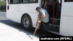 A disabled man is helped off a bus in Ashgabat by a fellow passsenger. (file photo)