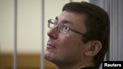 Former Interior Minister Yuriy Lutsenko looks on from the defendant's cage in court in Kyiv in July.
