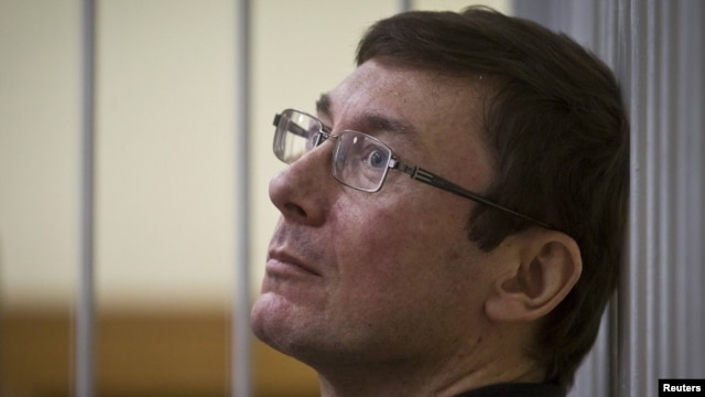 Former Interior Minister Yuriy Lutsenko looks on from the defendant's cage as he attends court session in Kyiv last year.