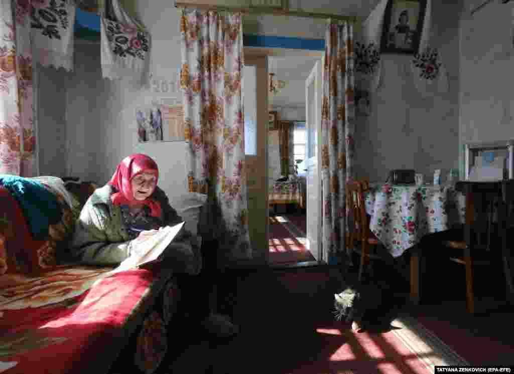 Kataryna Bidnosheya studies her ballot papers in the village of Velyki Dmytrovychi, central Ukraine. (EPA-EFE / Tatyana Zenkovich)
