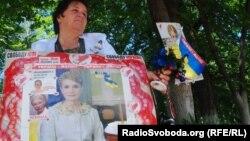Юлия Тимошенконың суреті басылған плакат ұстаған әйел оның босатылуын талап етіп, пикет өткізіп тұр. Харьков, 19 мамыр 2012 жыл.