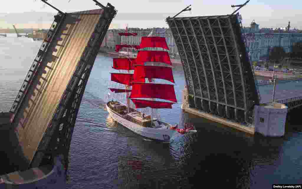 A ship with scarlet sails travels through a drawbridge rising above the Neva River in St. Petersburg, Russia. (AP/Dmitri Lovetsky)