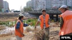 Рабочие убирают побережье реки Сазды в Актобе накануне саммита Казахстана и России.
