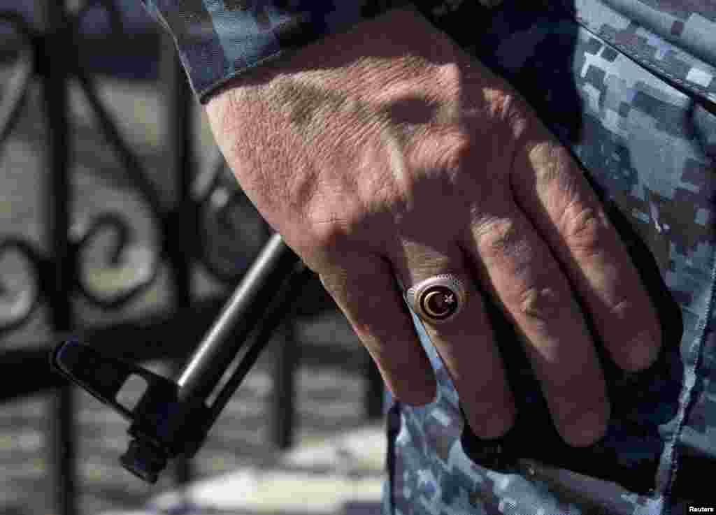 A policeman wears a ring showing the Islamic symbol of the star and crescent in the village of Itum-Kale.