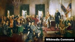 """""""Подписание Конституции Соединенных Штатов"""". Художник Говард Чандлер Кристи. 1940. На картине присутствуют 40 из 55 делегатов Конституционного Конвента. Стоит на подиуме Джордж Вашингтон, в центре сидит в кресле Бенджамин Франклин, слева от него – Александер Гамильтон, справа за столом – Джеймс Мэдисон, за его спиной стоит с поднятой рукой Дэвид Брэдли. Слева с вытянутыми руками – братья Чарльз и Чарльз Котсуорт Пинкни, предлагавшие избирать президента Конгрессом"""