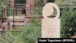 """Временное деревянное надгробие на могиле 49-летнего Таира Калдыбаева на кладбище """"Кенсай-2"""". Алматы, 8 июля 2016 года."""
