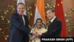 Russian Foreign Minister Sergey Lavrov (L), Indian External Affairs Minister Sushma Swaraj (C), and Chinese Foreign Minister Wang Yi pose for a photograph ahead of a trilateral meeting in New Delhi on December 11.